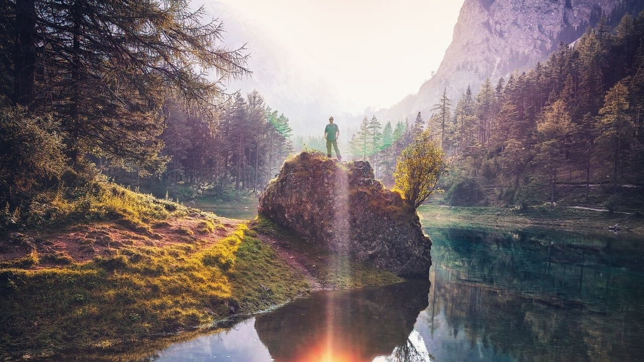 man on rock with nature trees and river