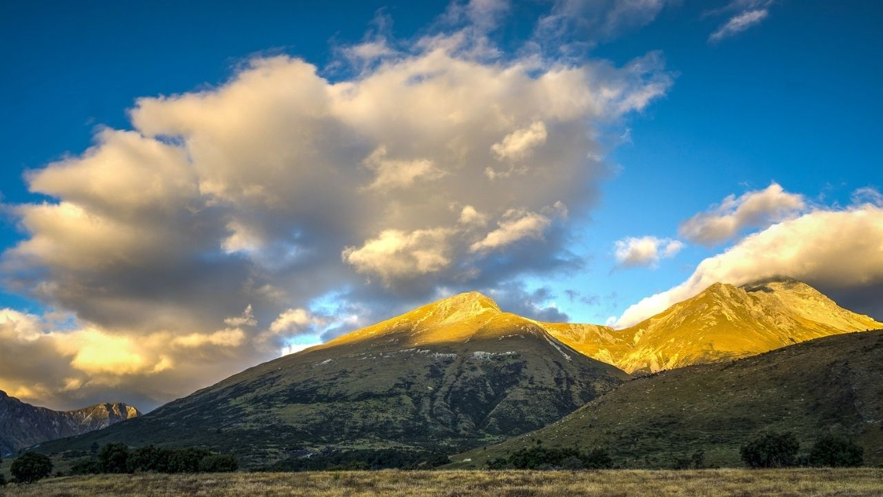 sun landing on mountain tops from behind clouds