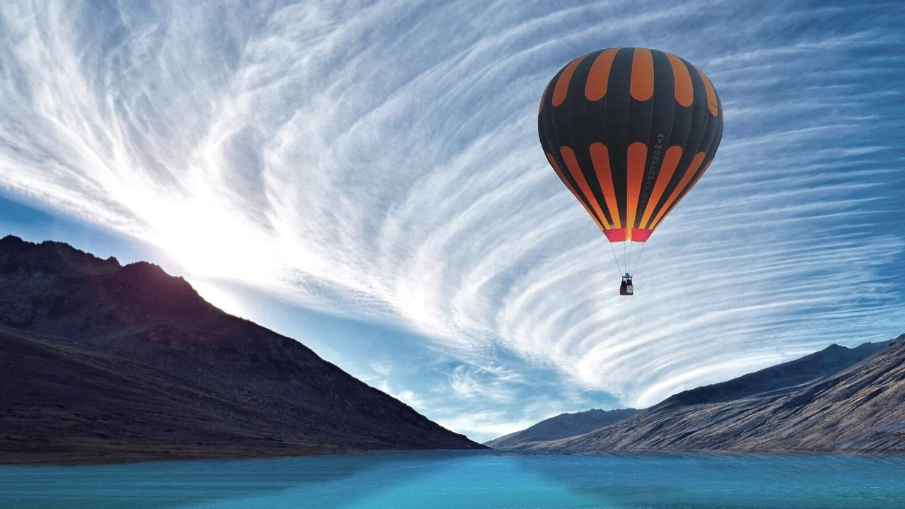 hot air balloon over water heading to mountains