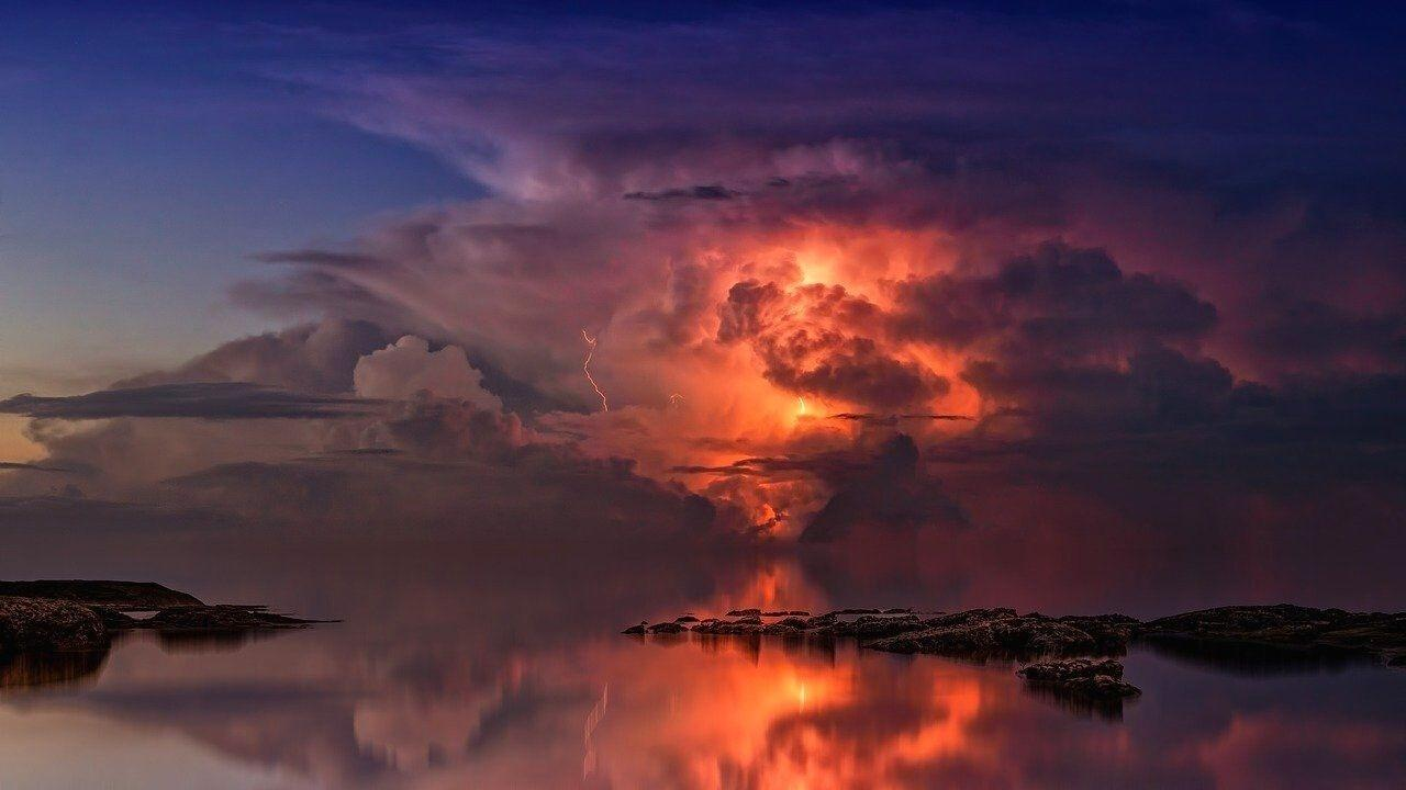 Moody clouds and thunderstorm over sea and rocks