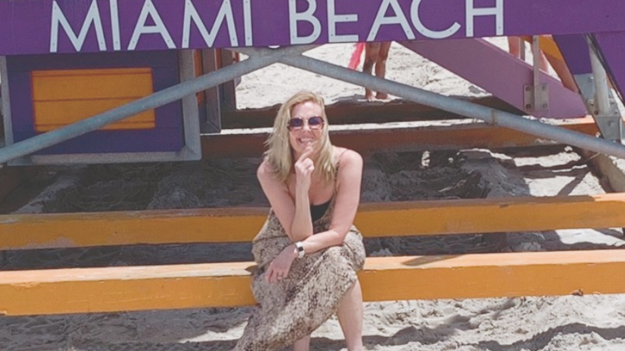Lori Massicot sitting by a Lifeguard station that says MIami Beach