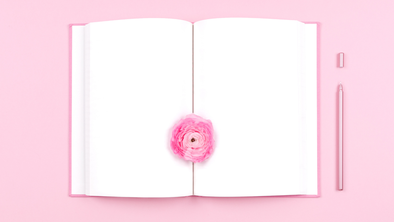 Opened journal with blank page, pink pen and a pink flower in the middle.