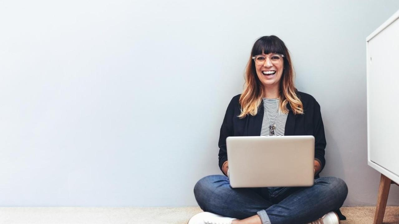Creative woman with laptop smiling.