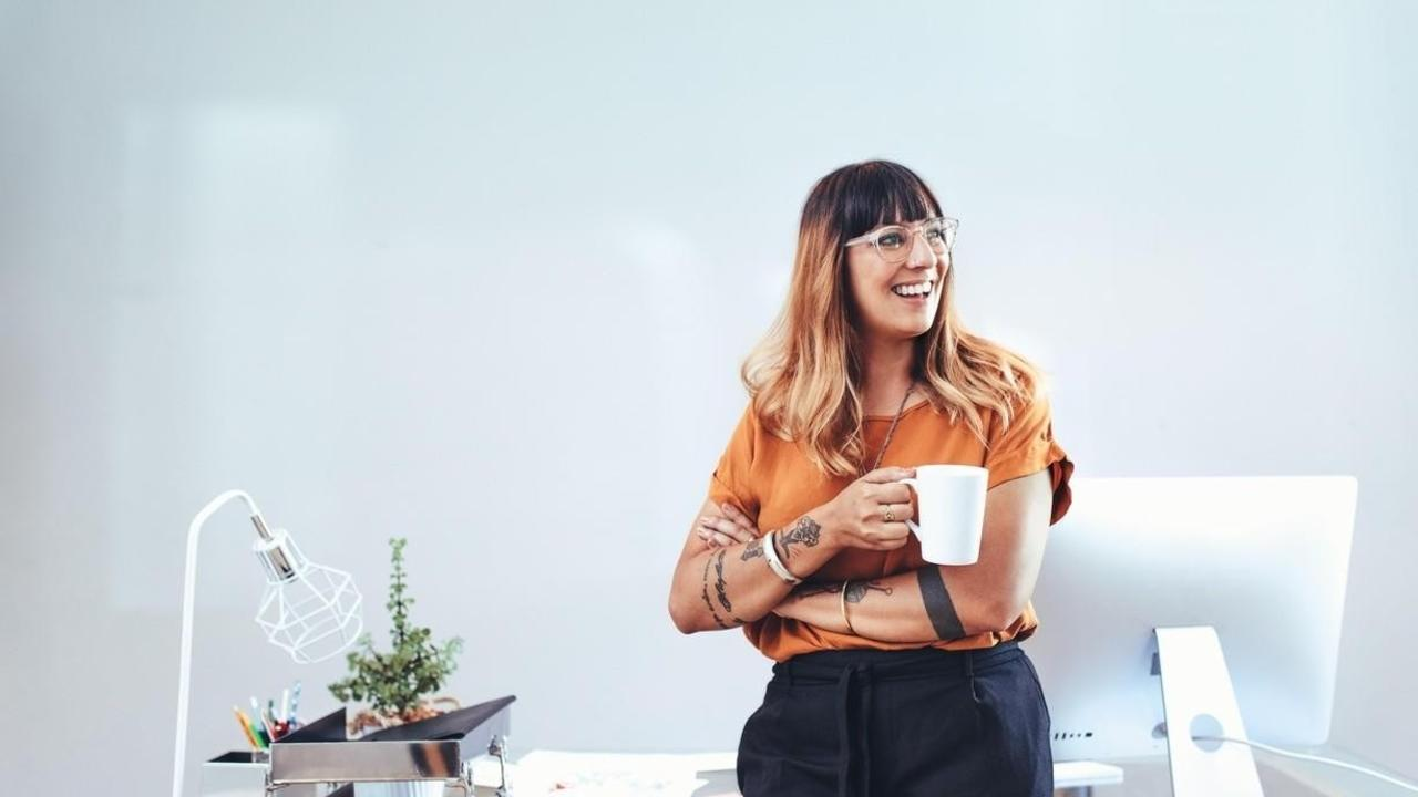 Woman by desk with coffee cup.