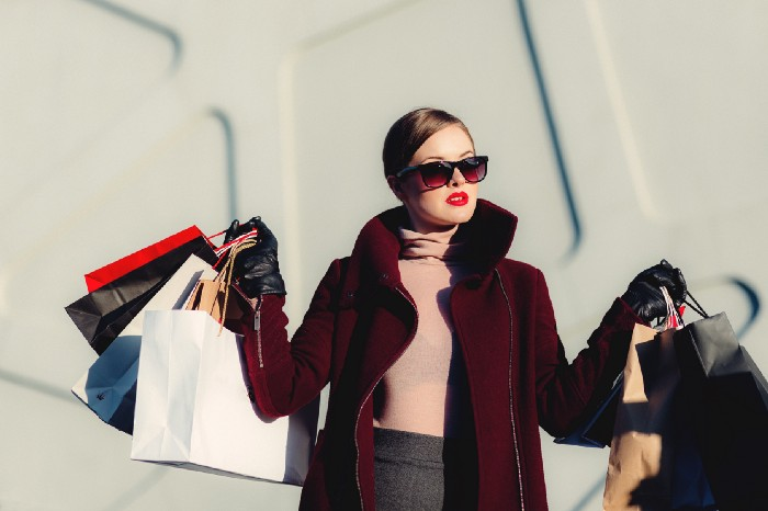 rich woman wearing sunglasses leaving mall with lots of shopping bags