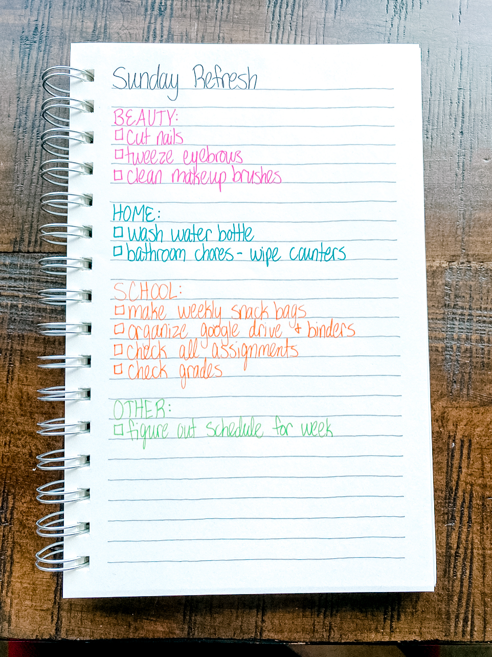 Photo of a notebook with a handwritten to-do list with color-coded categories.