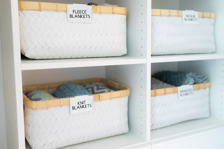 Photo of labeled baskets with neatly folded blankets.