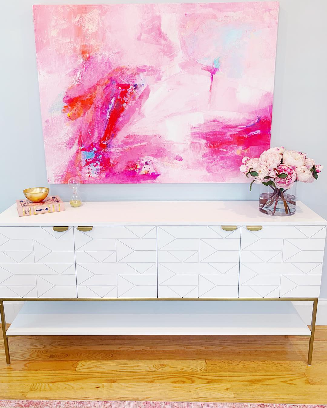 White console table with pink painting above.