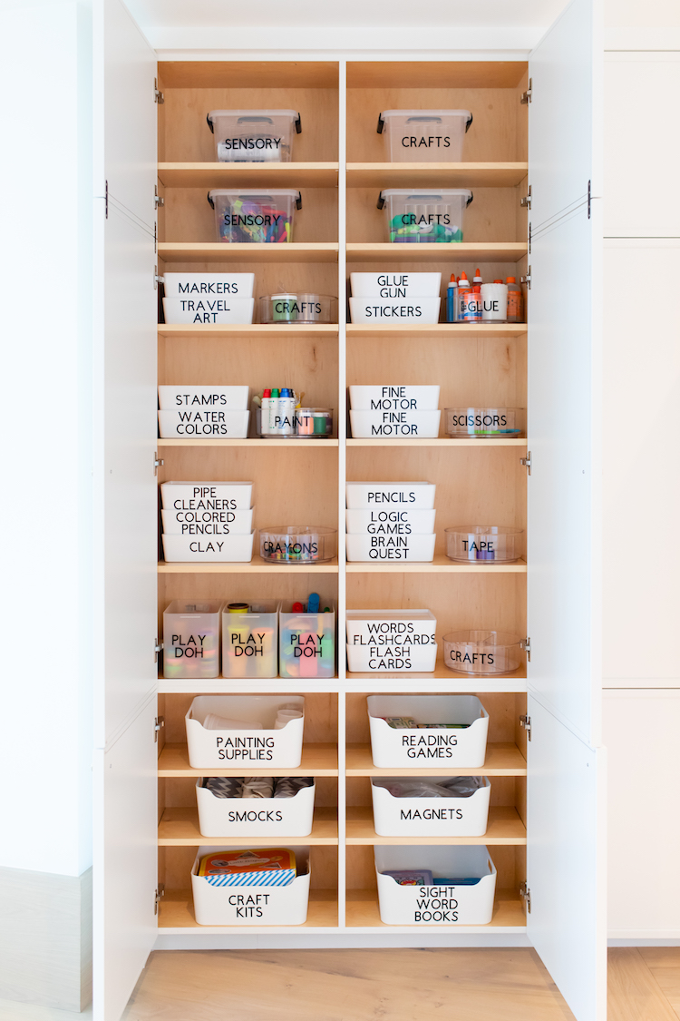 Tall, organized cabinet with white bins and black labels.