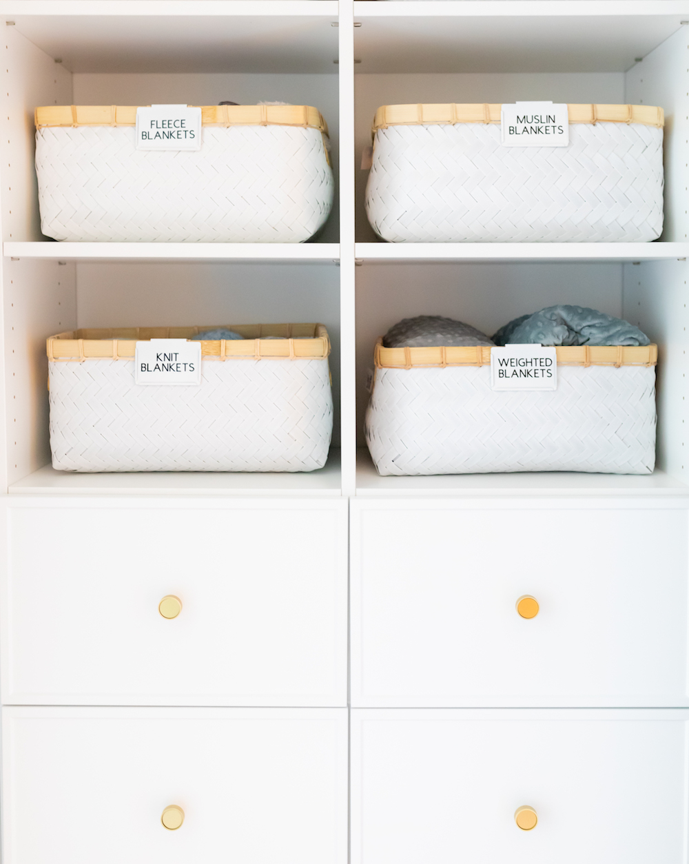 White cabinet with white baskets labeled for blankets.