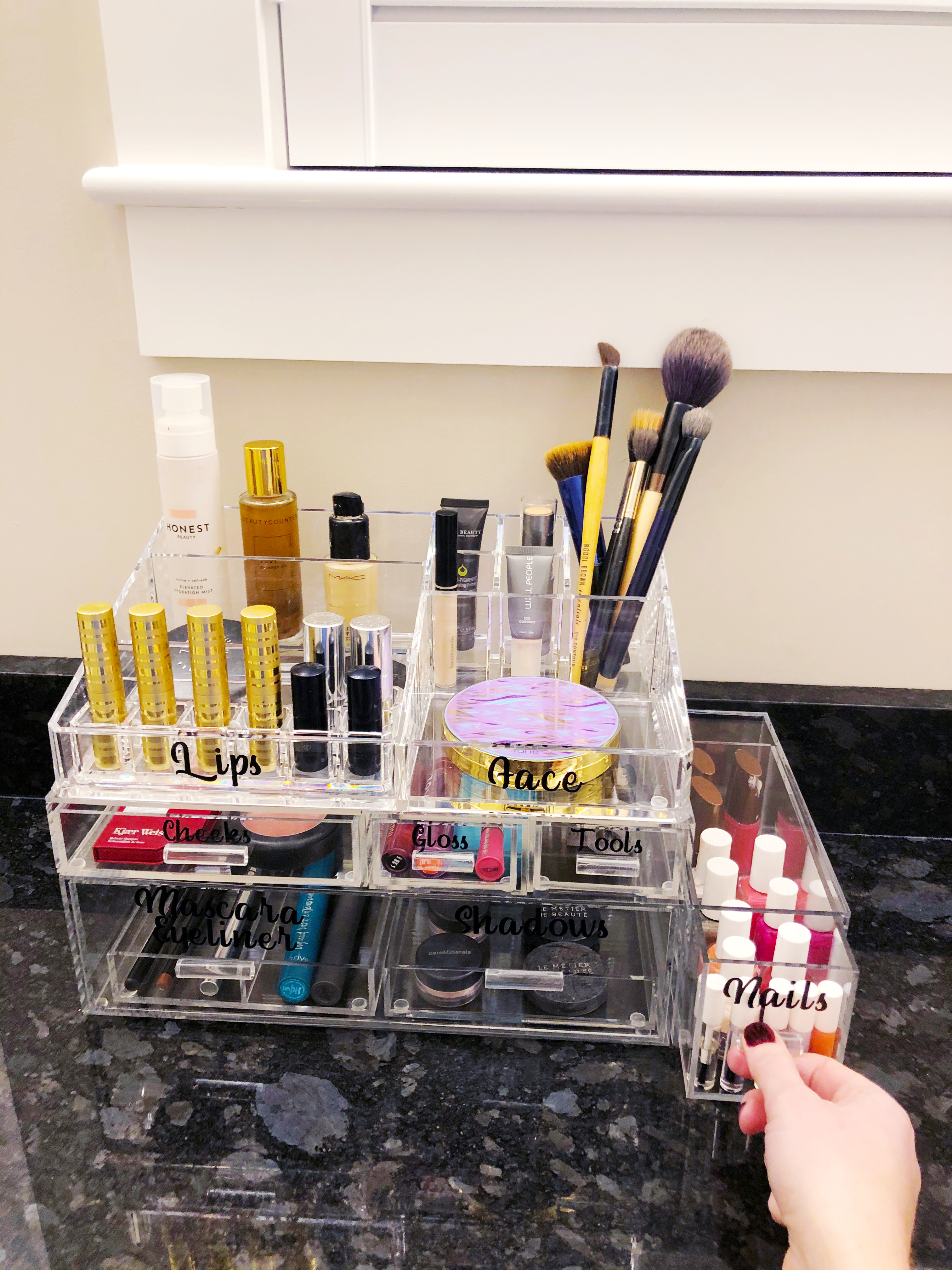 Container for easily organizing your makeup, with a focus on a long drawer for nail products.