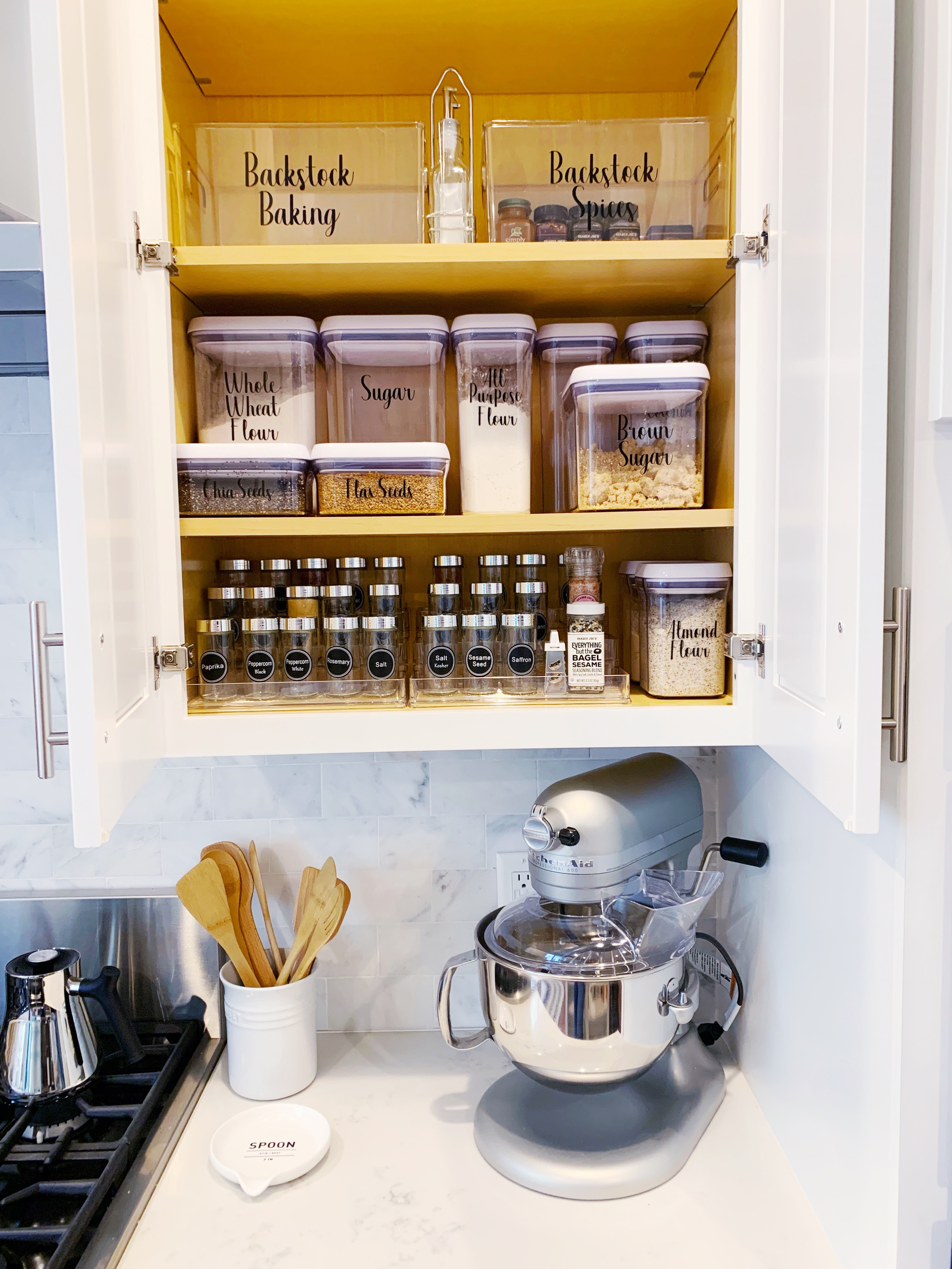 Kitchen cabinet organized with coordinating bins and containers.