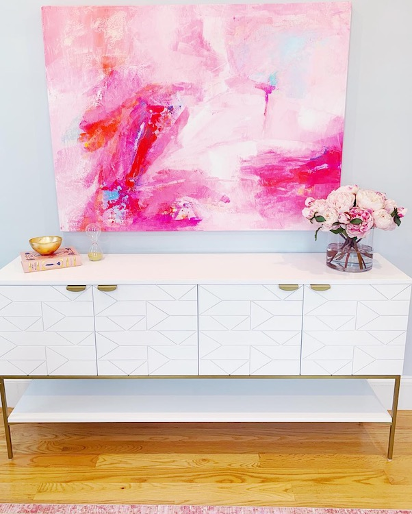Neatly organized white buffet table with decorative flowers and books with a pink modern art hanging above it.
