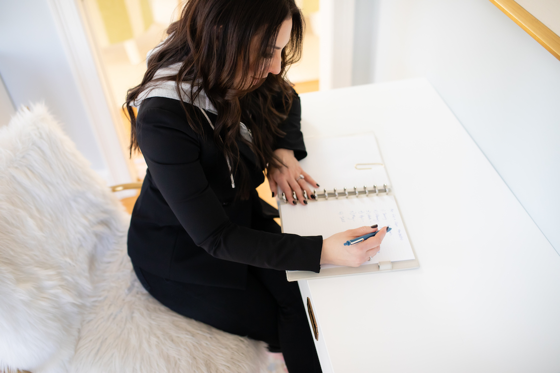 Woman smiling and sitting at her white desk in her office writing on a pad of paper..