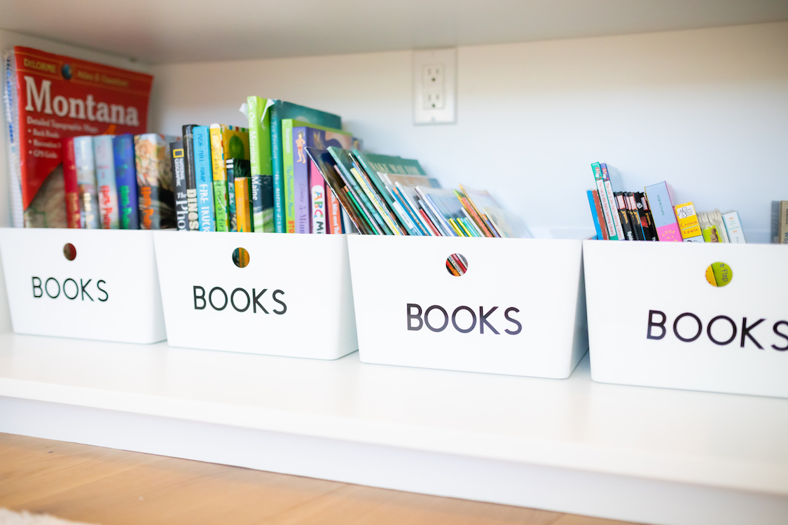 Photo of white shelf with white bins and colorful children's books.