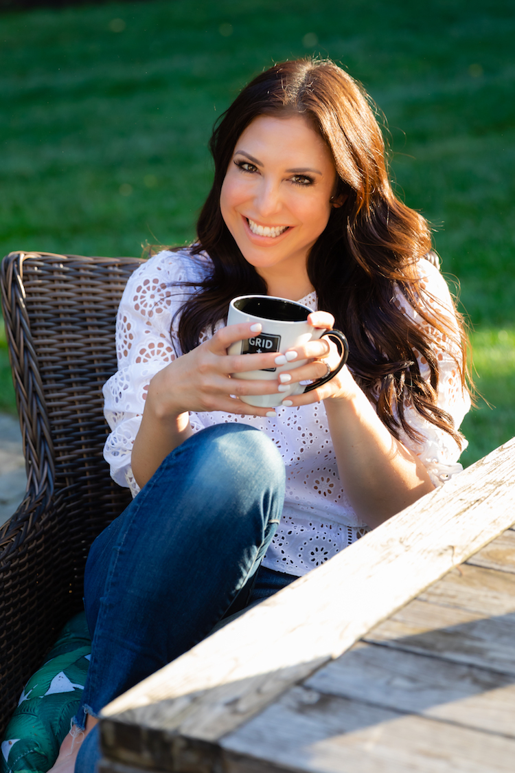 Business woman sitting at picnic table with coffee smiling at camera.