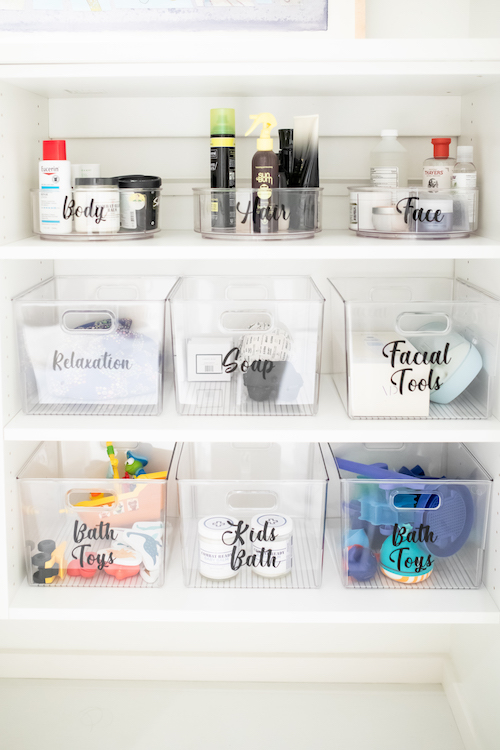 Organized bathroom with see-through bins and black labels.