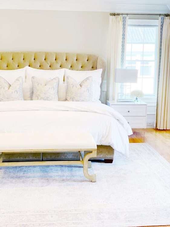High end, queen-sized bed with white bedspread in a neatly organized bedroom.
