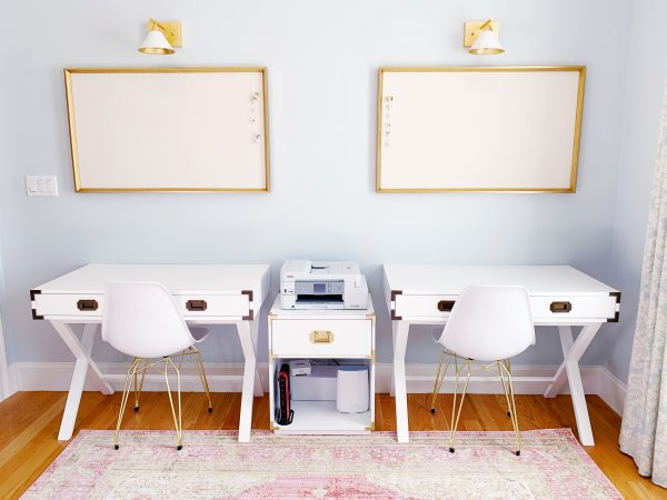 Photo of two white office desks with a pink rug underneath them.