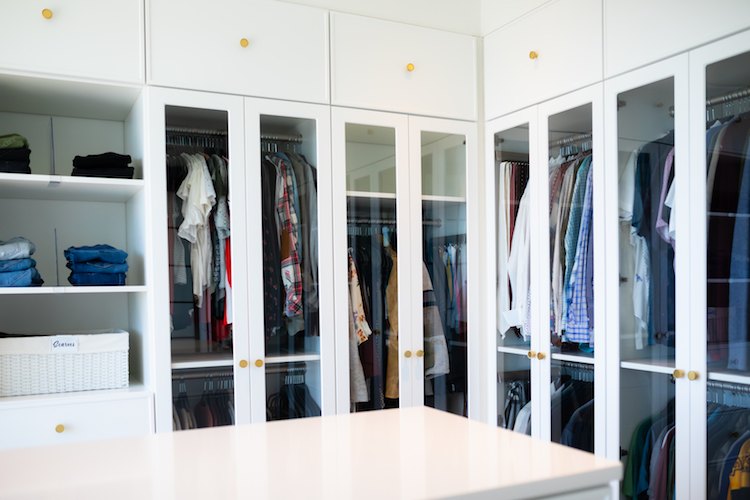 Photo of a large, organized closet with built in shelving.