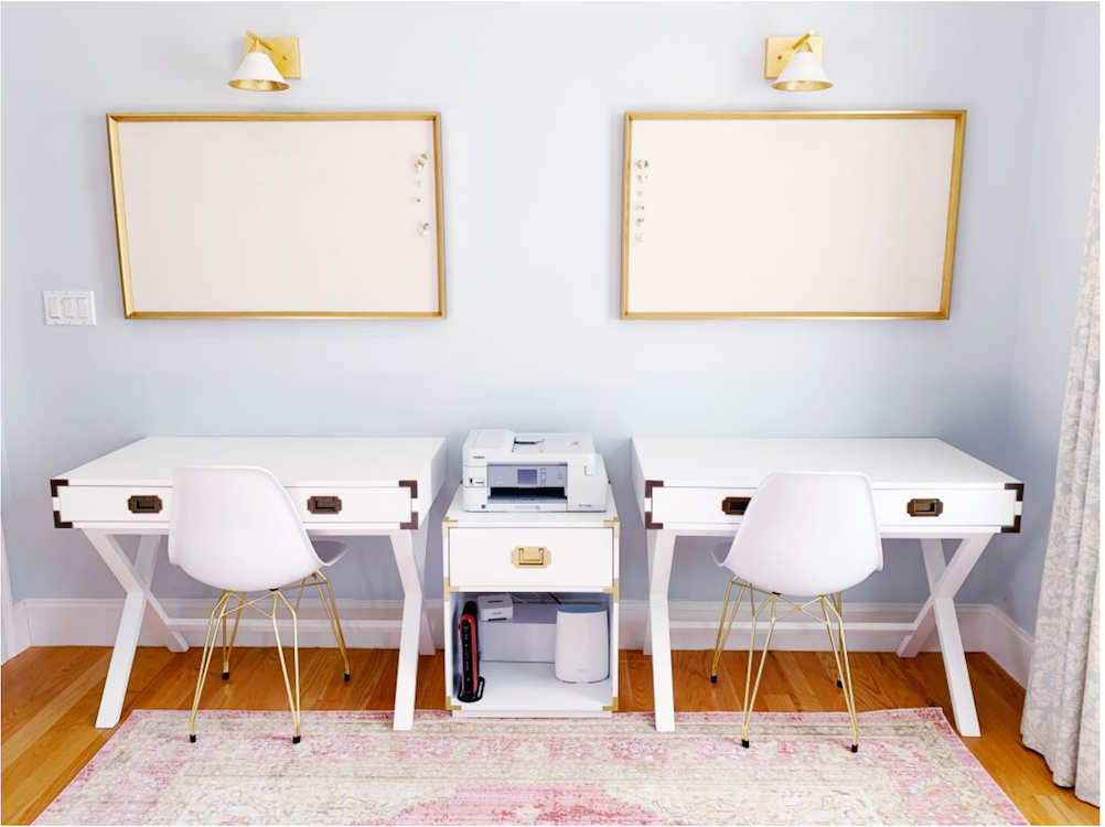 Two white desks in a neat and organized home office with matching gold cork boards above them.