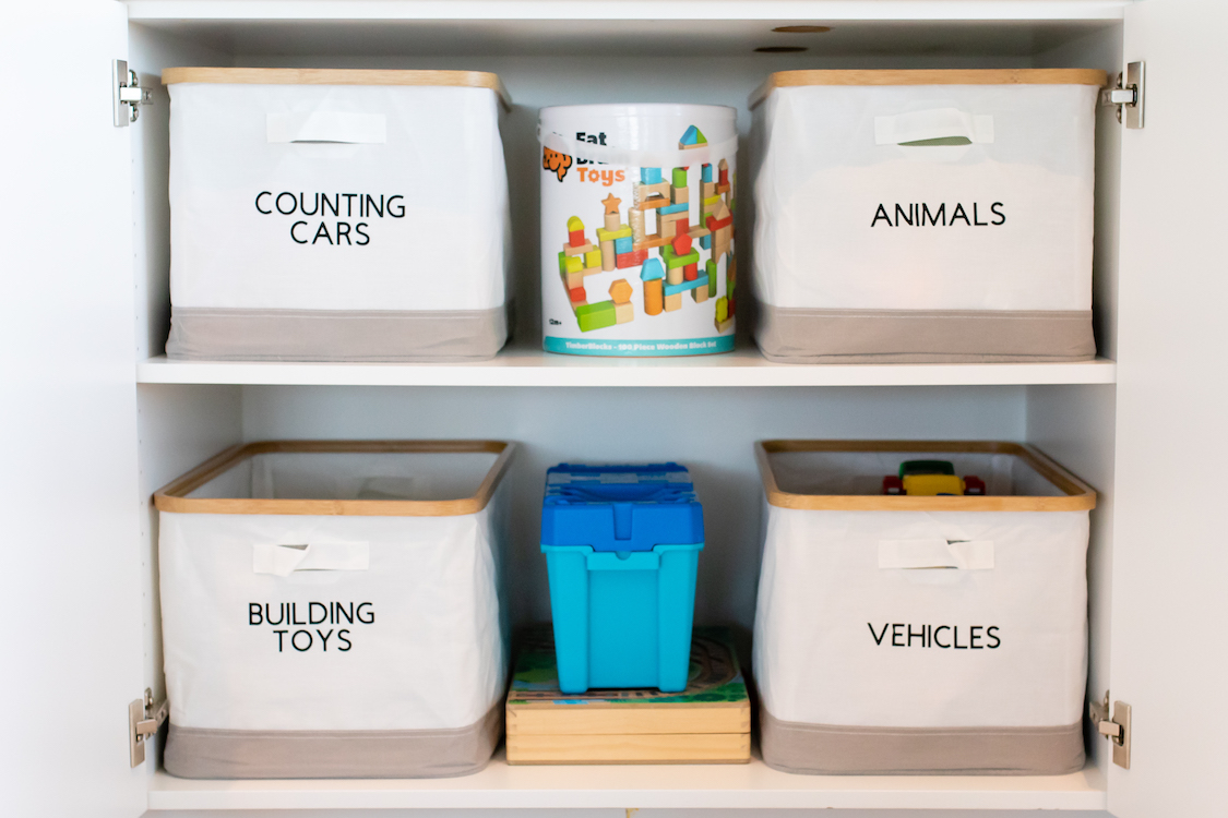Photo of a white shelf with bins of toys.