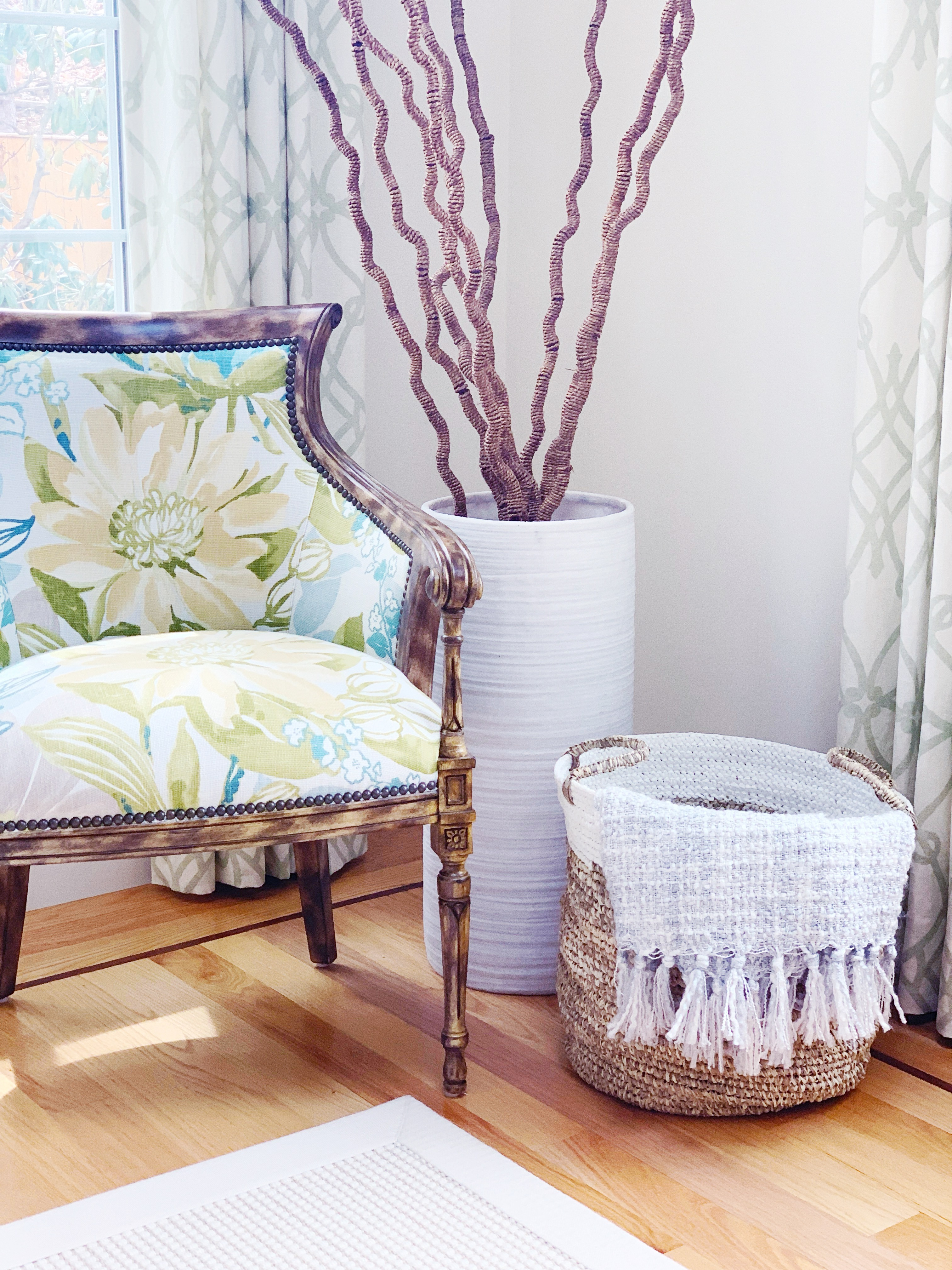 Reading corner in a bedroom with a floral chair and basket on the floor