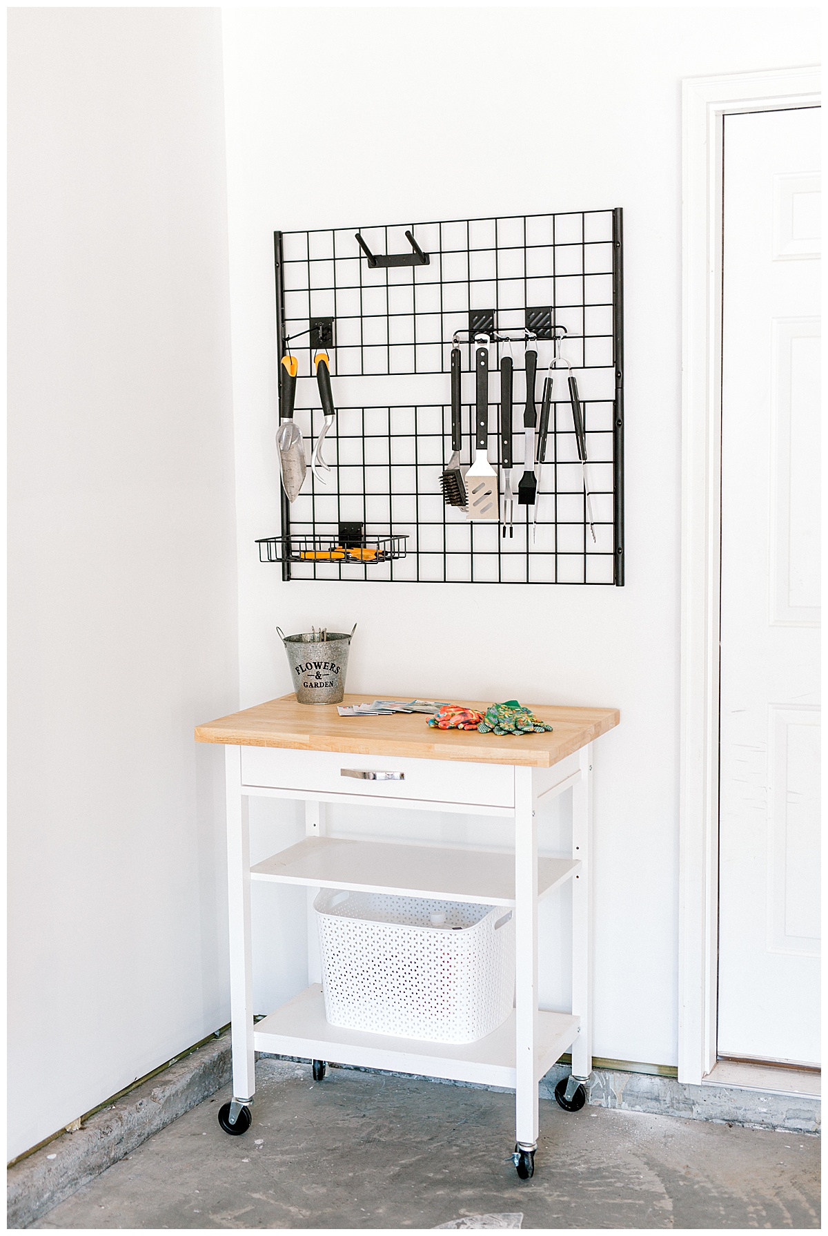 Photo of a corner of a garage with a cart sitting underneath an organizer for gardening tools.