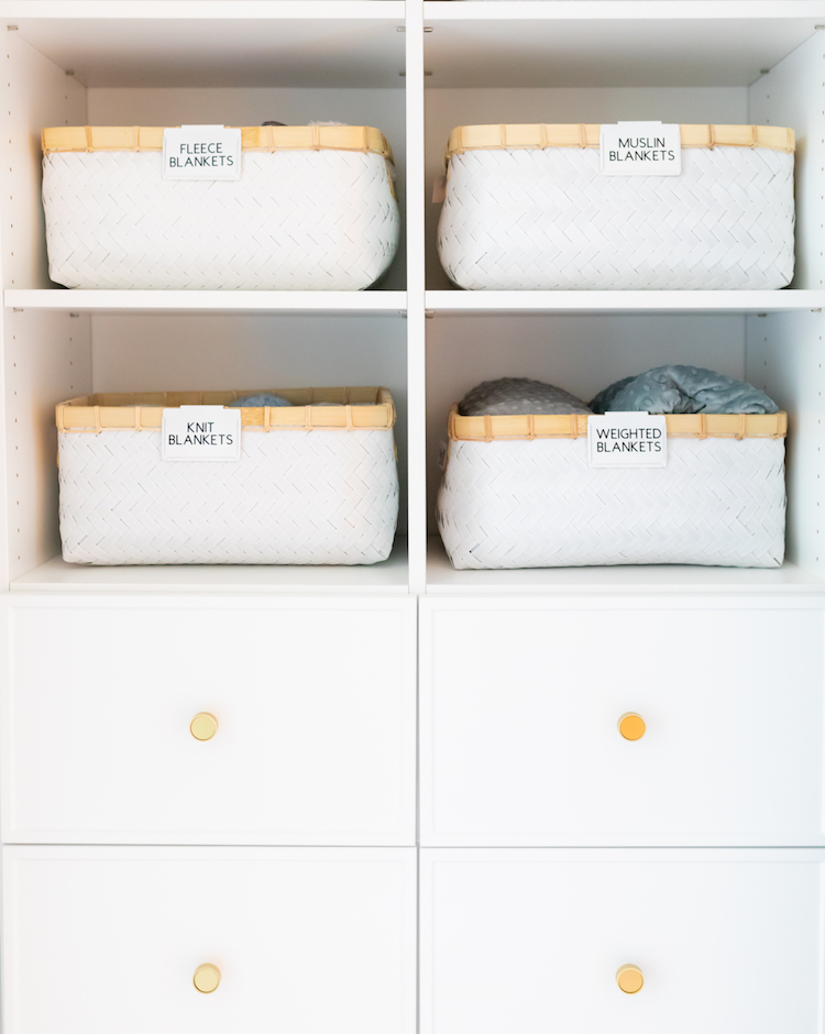 Photo of a white cabinet with baskets labeled for blankets.