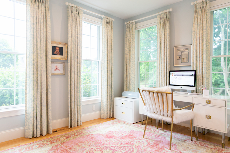 Photo of a clean, organized office with white furniture and a pink rug.