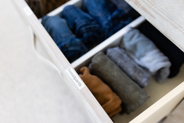 Organized, labeled drawer with neatly folded pants.