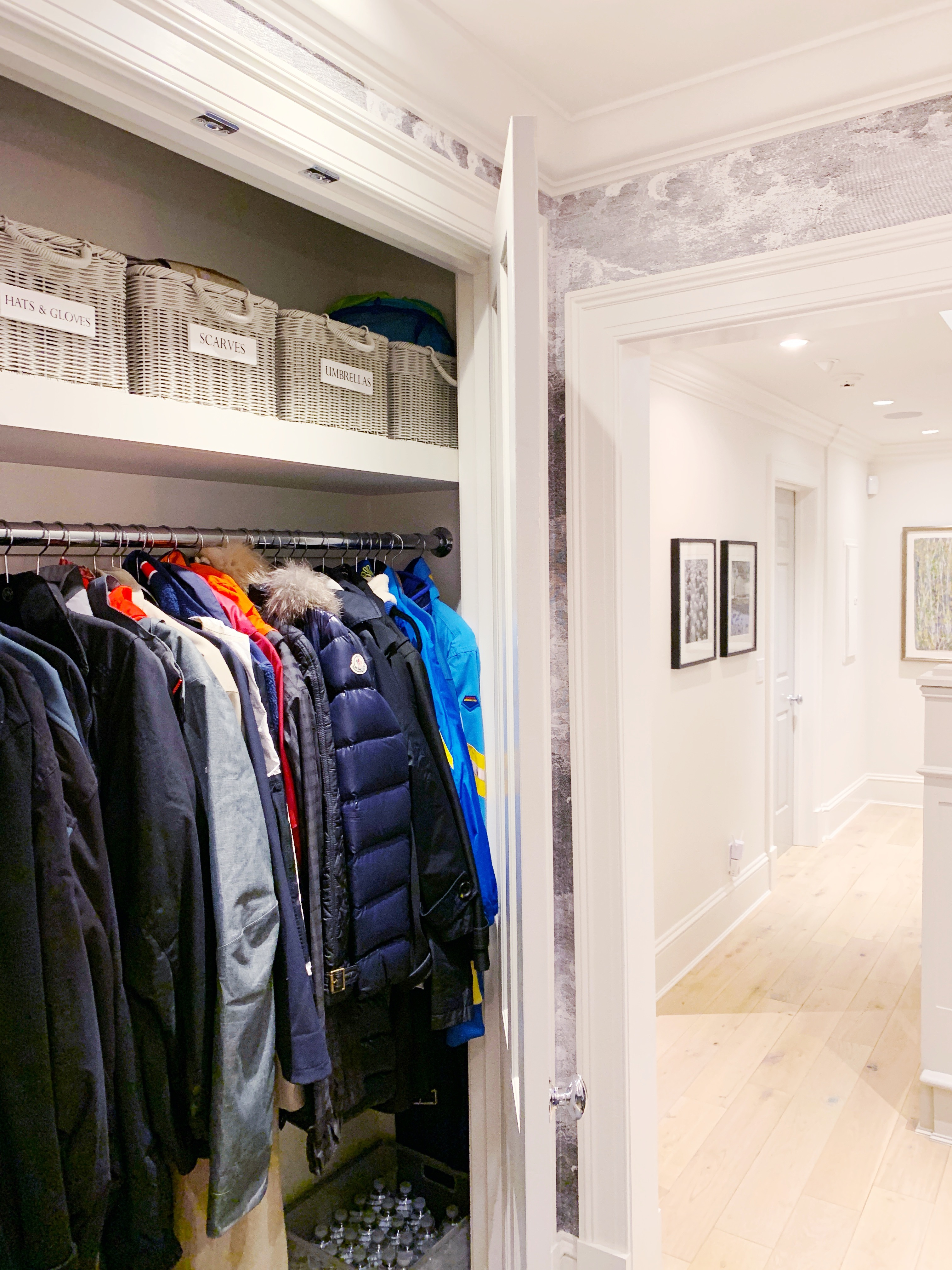 Closet organization system with matching grey baskets on the top shelf.