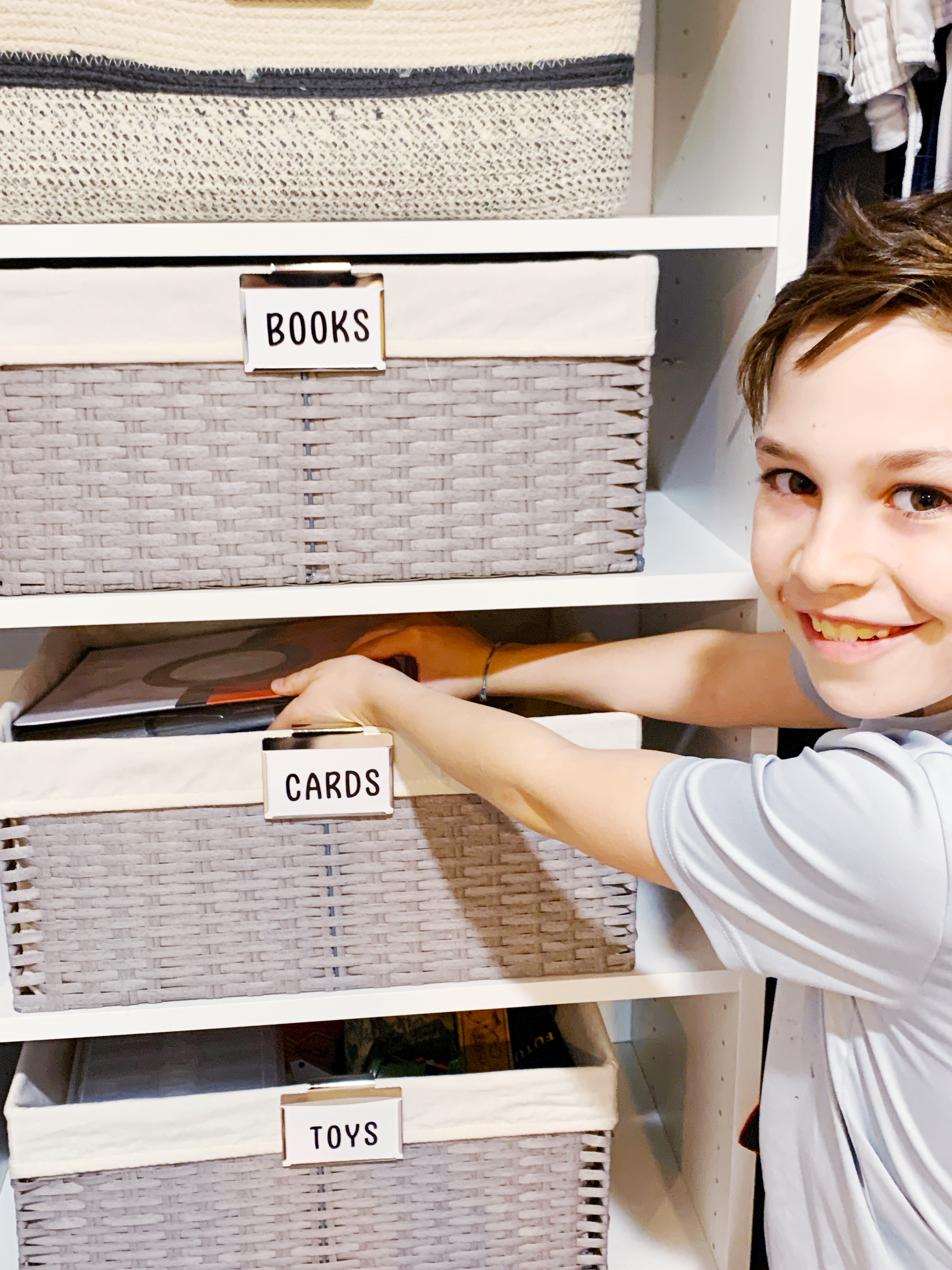 A child helping keep his room tidy with new bins