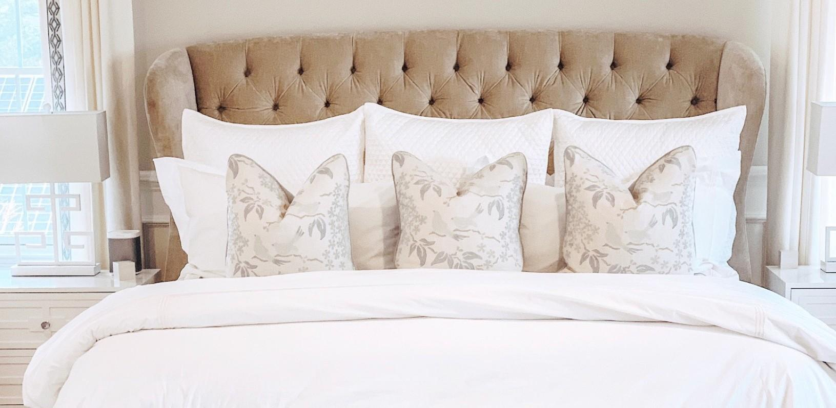 High-end, made bed with neutral colored throw pillows.