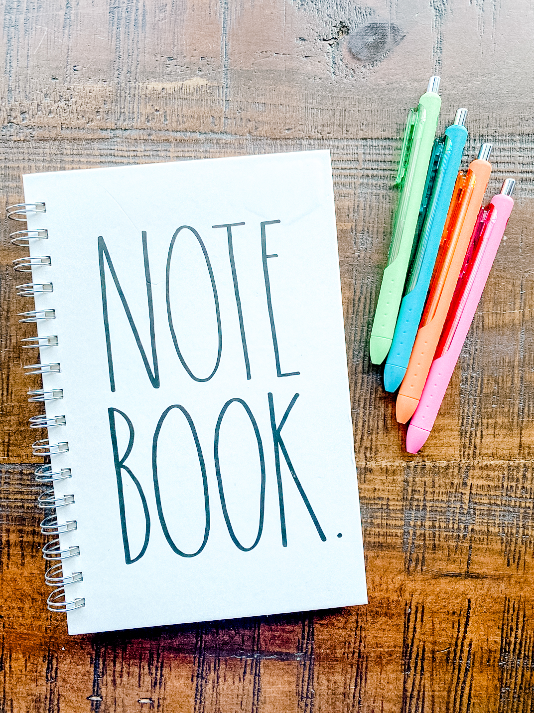 White notebook with multiple colored pens.