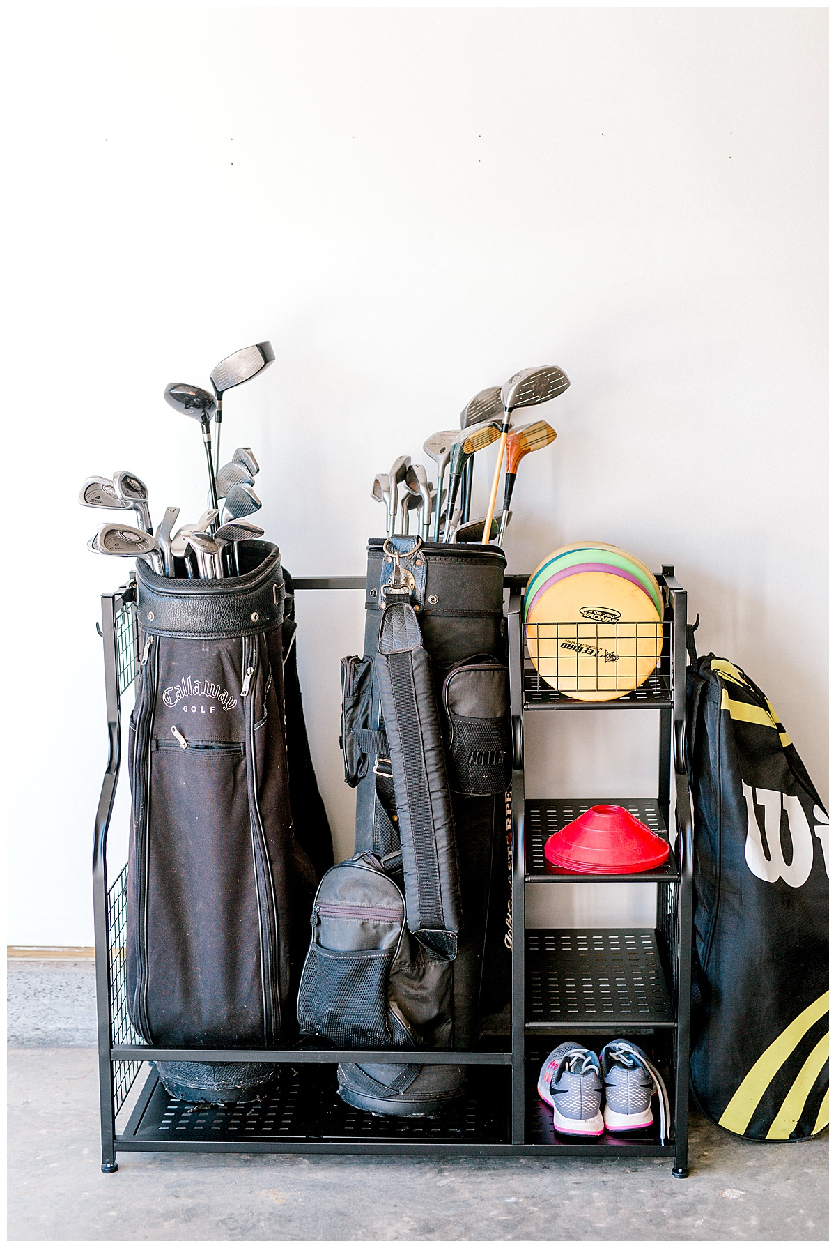 A garage organizer for gold equipment with two golf bags and a pair of shoes.