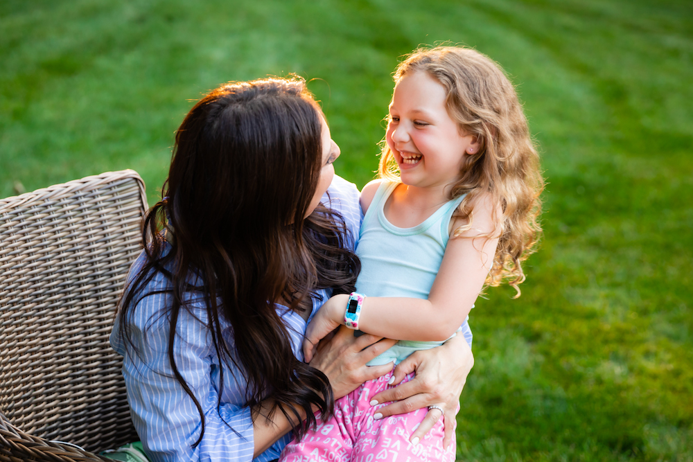 Woman and her daughter laughing together outside during the Spring.