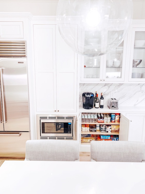 Clean, while, well-organized kitchen with classy beverage bar.