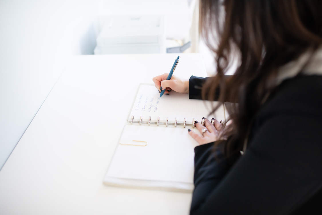 Photo of a woman's hands writing on a pad of paper on a white desk.