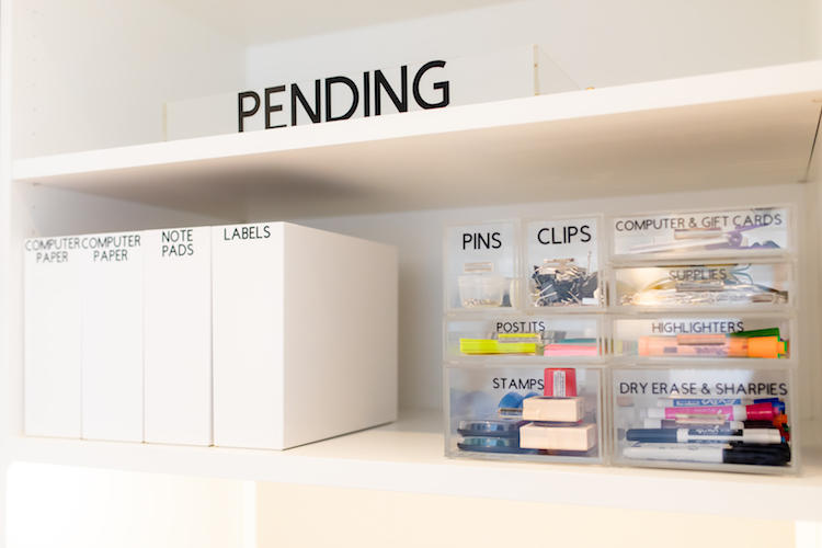 Professionally organized shelf with bins for pending papers and small, labeled baskets for office supplies.