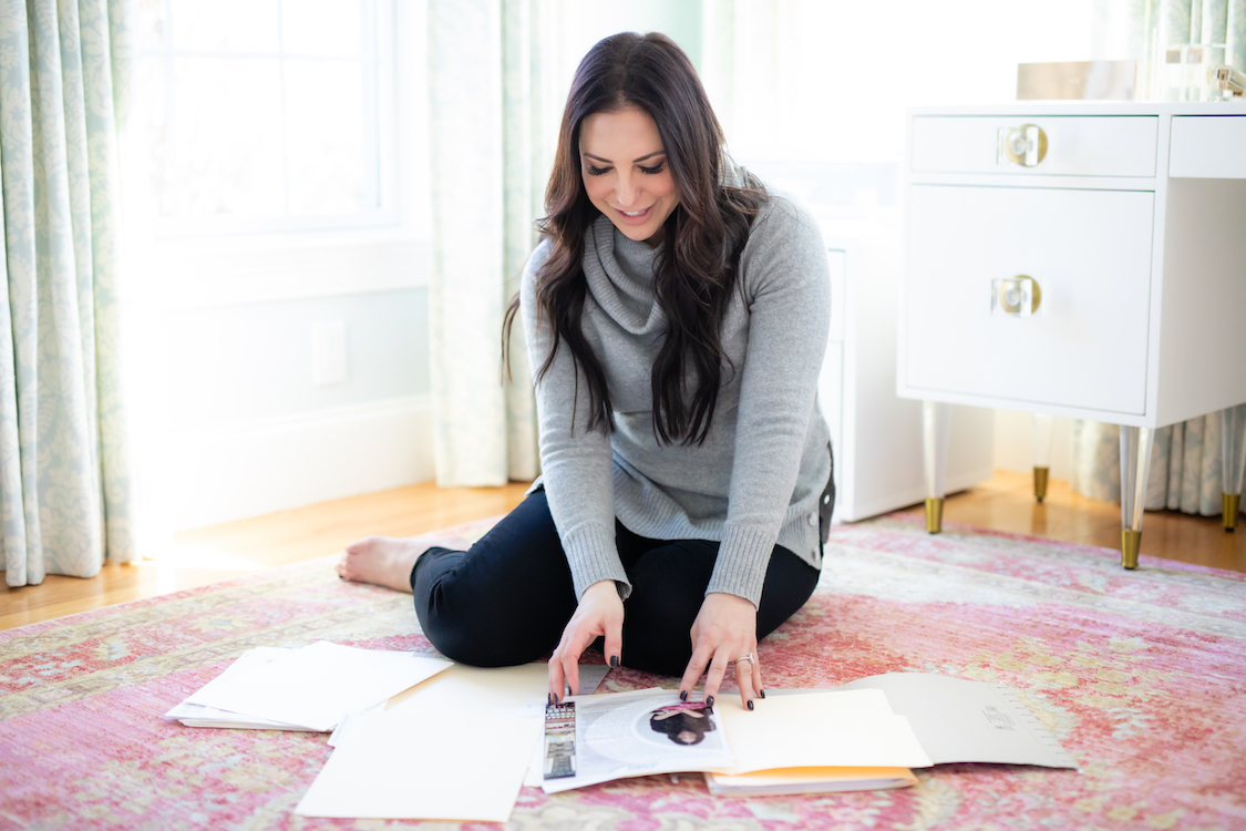 Professional organizer organizing paperwork on the floor of her office.