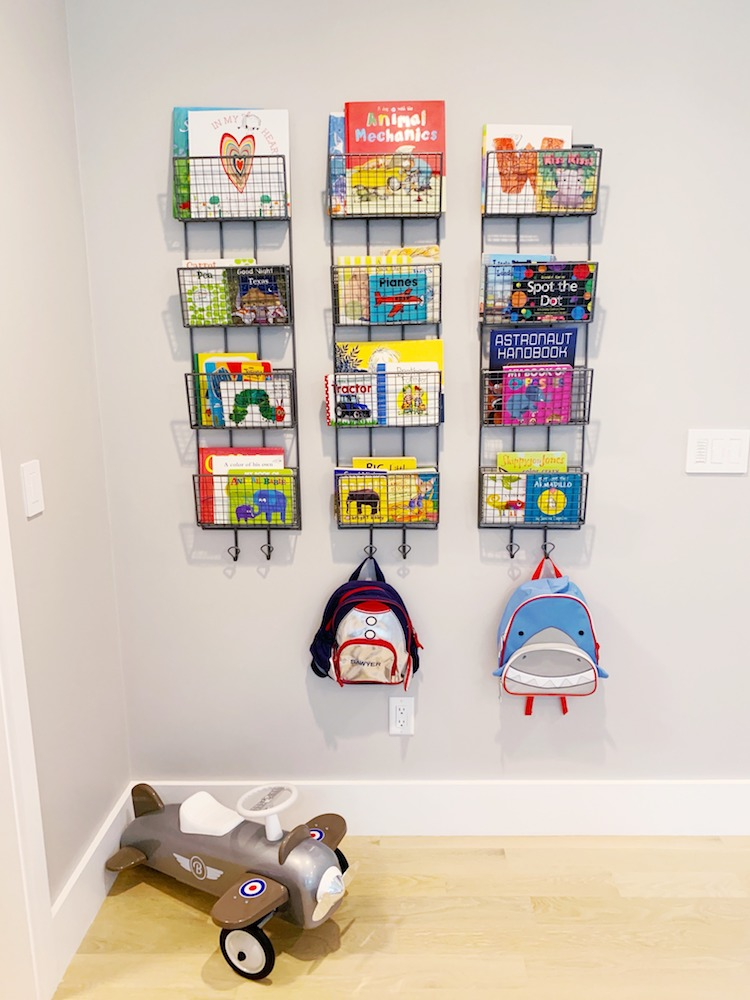 Creative book shelf on the wall of a kids rooms filled with colorful children's books.