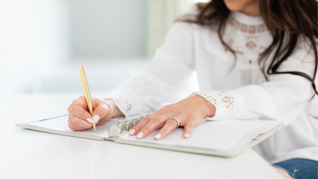 Female professional organizer writing in a notebook