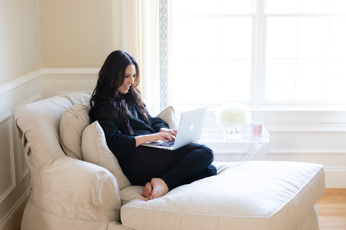 Women in a black top sitting on her couch typing on her laptop.