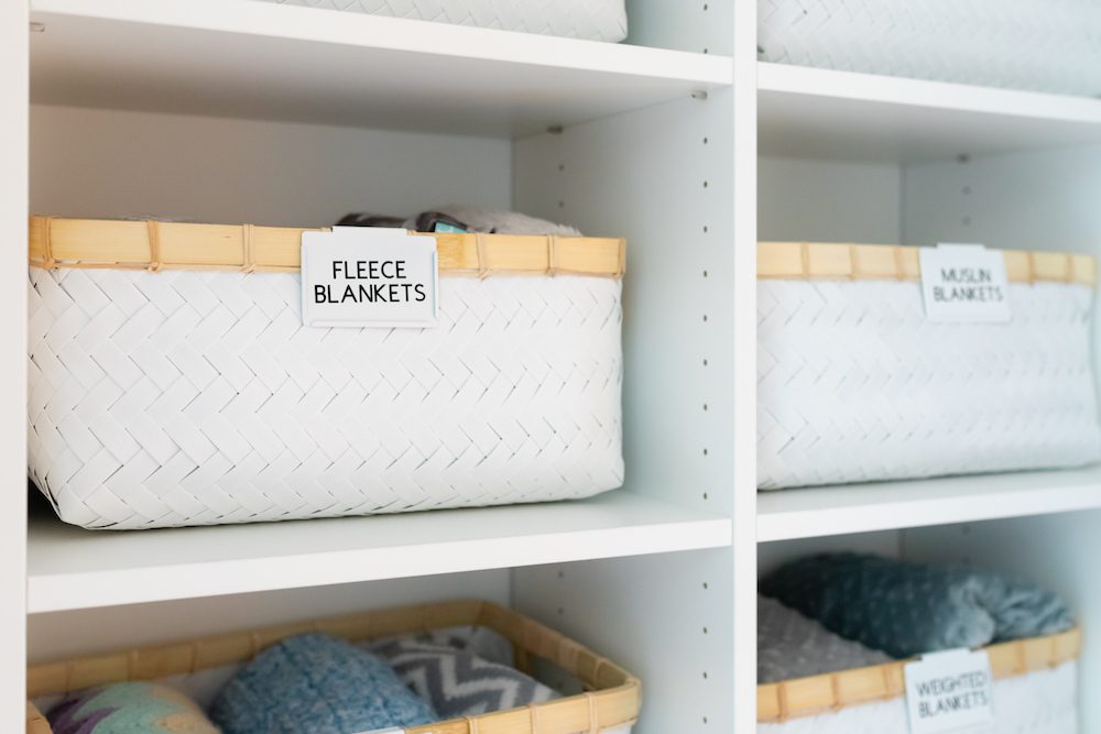 White woven baskets labeled for blankets.