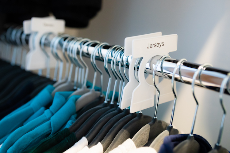 Clothing hanging on a rod, with labeled dividers.