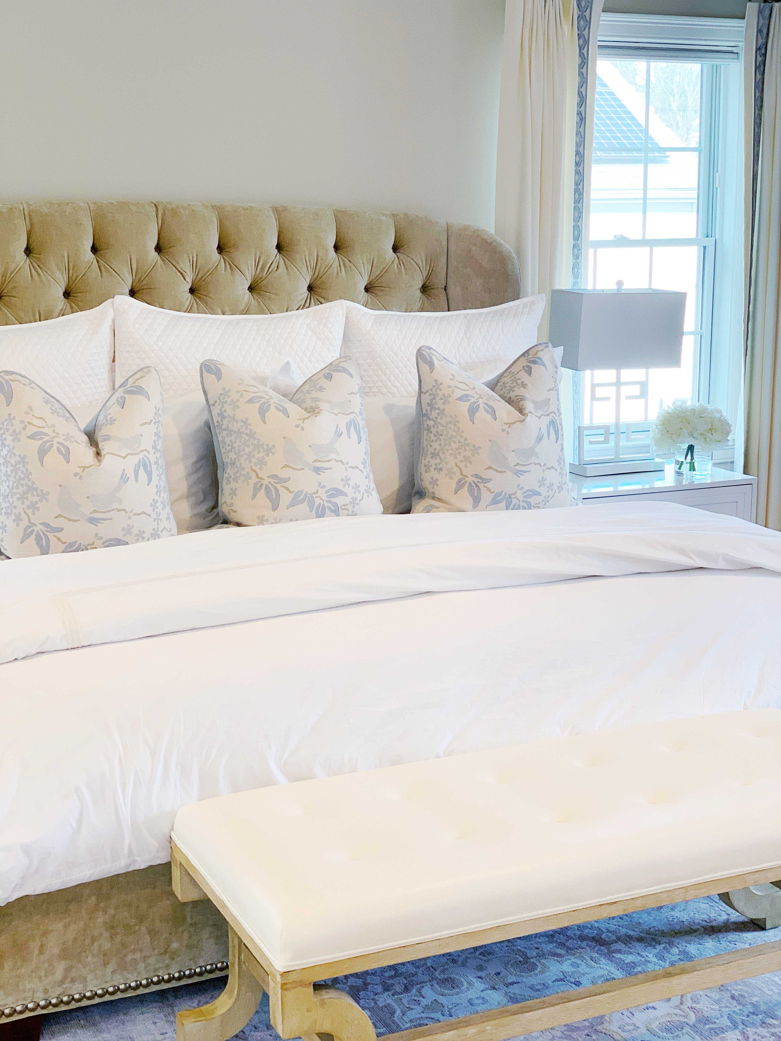 Neatly made bed with neutral colored throw pillows.