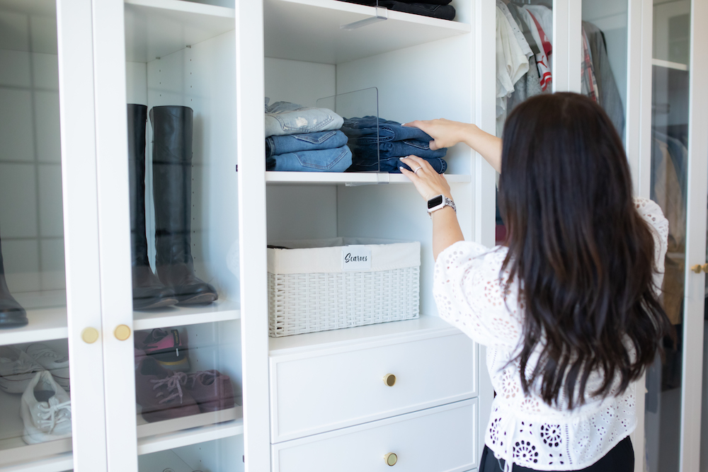 Professional organizer putting away neatly folded item in an organized closet.
