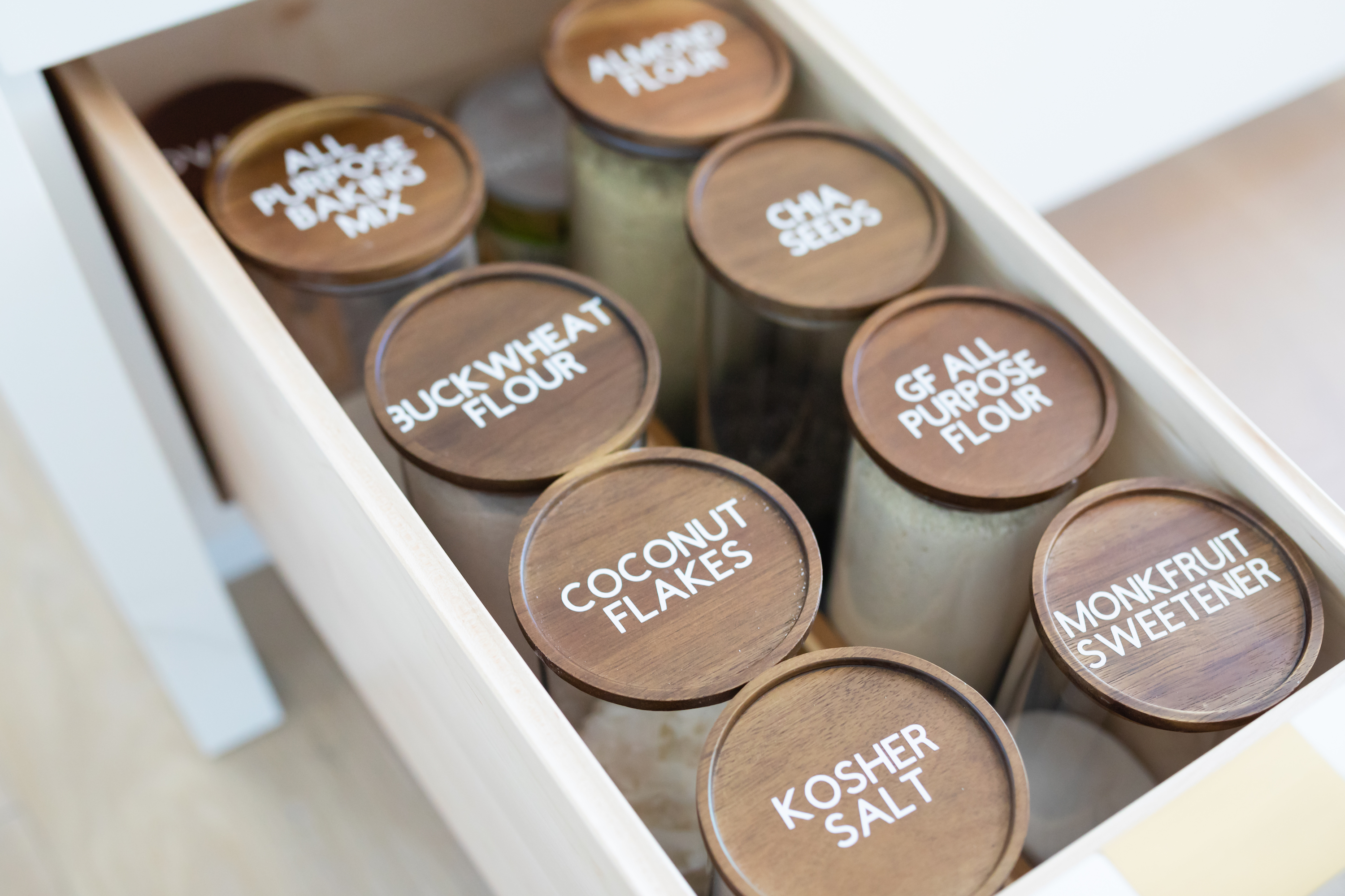 Photo of a kitchen drawer with high-end spice containers with white labels.