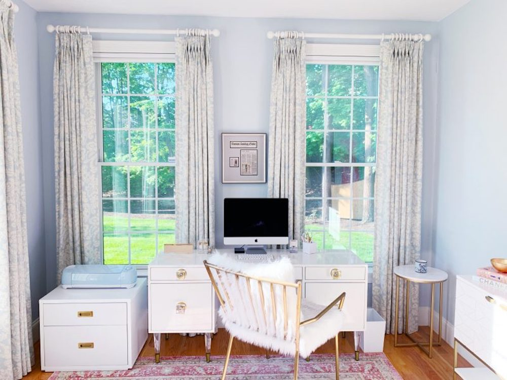 Organized home office with clean white furniture and a frilly chair.